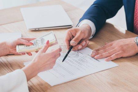 Photo pour Vue partielle de l'homme d'affaires pointant à la signature lieu dans l'accord de prêt près du client détenant de l'argent - image libre de droit