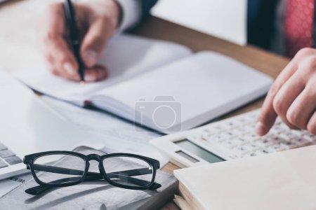 Photo pour Plan recadré de l'homme d'affaires écrit dans un carnet vide tout en utilisant la calculatrice - image libre de droit