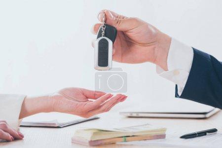 Photo pour Partial view of businessman giving car keys to customer in office - image libre de droit