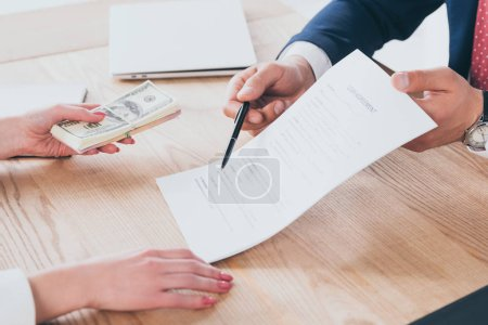 Photo for Partial view of businessman pointing at signature place in loan agreement near woman holding dollar banknotes - Royalty Free Image