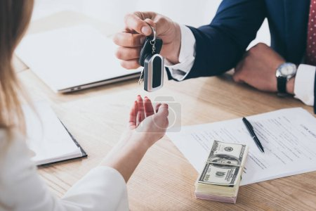 Photo pour Partial view of businessman giving car keys to customer near dollar banknotes and loan agreement - image libre de droit