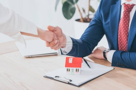 Photo pour Partial view of businessman and client shaking hands near house model on table - image libre de droit