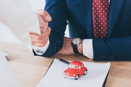 Photo pour Coup recadré de femme se serrant la main avec l'homme d'affaires près de la voiture rouge de jouet - image libre de droit