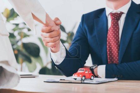 Photo pour Partial view of woman shaking hands with businessman near toy red car - image libre de droit