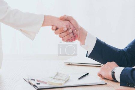 Photo pour Partial view of woman and businessman shaking hands in office - image libre de droit
