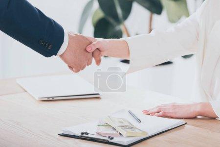 Photo pour Coup recadré de l'homme d'affaires se serrant la main avec le client dans le bureau - image libre de droit