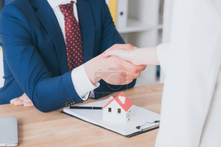Photo pour Partial view of customer shaking hands with realtor near house model - image libre de droit