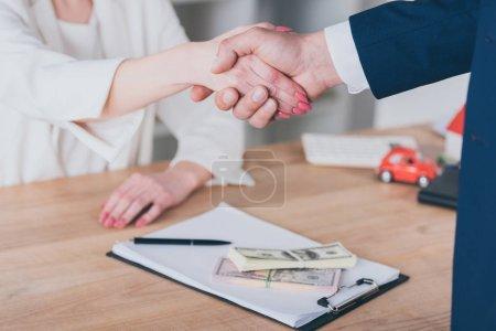 Photo pour Vue partielle de la femme serrant la main d'un homme d'affaires près des billets en dollars sur la table - image libre de droit