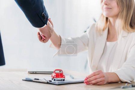 Photo pour Tir recadré de femme de sourire se serrant la main avec l'homme d'affaires près de la voiture rouge de jouet - image libre de droit