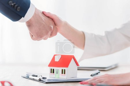 cropped shot of realtor shaking hands with client near house model on tabletop