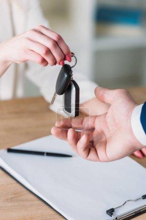 Photo pour Partial view of woman taking car keys from businessman in office - image libre de droit