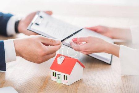 Photo pour Vue partielle de l'agent immobilier donnant le stylo et le presse-papiers avec l'accord de prêt au modèle proche de maison de client - image libre de droit