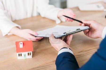 Photo pour Coup recadré ecitar ison de l'agent immobilier donnant stylo et presse-papiers avec accord de prêt au client près du modèle de maison - image libre de droit