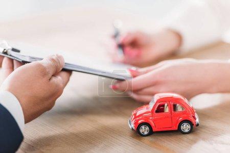 Photo pour Coup recadré e de concessionnaire automobile donnant un presse-papiers au client près de la voiture miniature - image libre de droit