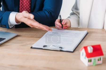 Photo for Partial view of businessman showing signature place in loan agreement to client holding pen - Royalty Free Image