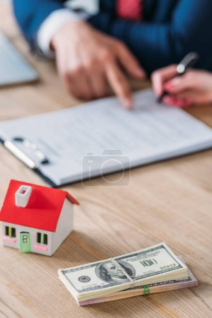 Photo pour Partial view of businessman pointing at signature place in loan agreement near house model and dollar banknotes on table - image libre de droit