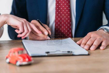 Photo pour Partial view of car deal pointing at signature place in loan agreement near client holding pen - image libre de droit