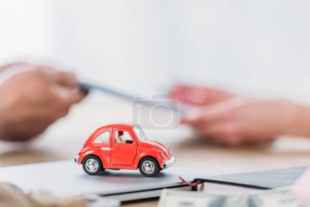 Photo for Partial view of businessman and customer near red toy car in office - Royalty Free Image