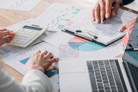 Photo pour Partial view of man studying loan agreement and businesswoman using calculator while sitting at workplace with graphs and charts - image libre de droit