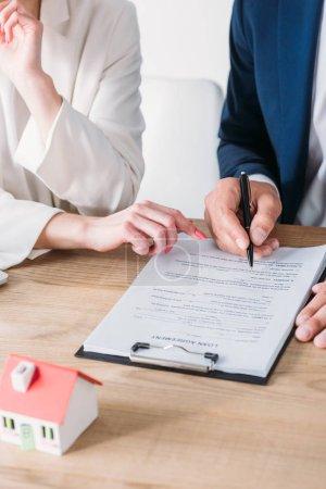 Photo pour Vue recadrée de l'homme signant l'accord de prêt près de la femme d'affaires pointant au lieu de signature - image libre de droit