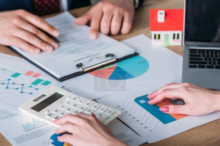 Photo for Partial view of man studying loan agreement and businesswoman using calculator while sitting at workplace with house model, graphs and charts - Royalty Free Image