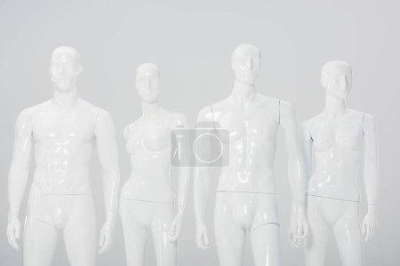 Photo for White plastic dummies in row isolated on grey - Royalty Free Image