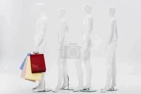 Photo pour Rangée de mannequins blancs avec des sacs à provisions sur le gris - image libre de droit