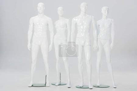 Photo for White plastic mannequins in row on grey - Royalty Free Image