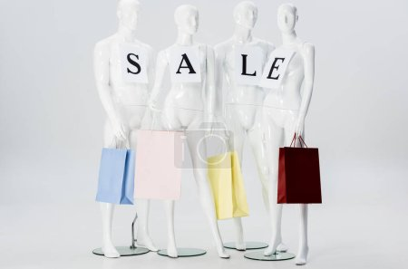 Photo for White mannequins with sale lettering on papers and shopping bags isolated on grey - Royalty Free Image