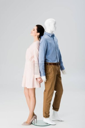 Photo for Beautiful girl holding hands with mannequin and smiling isolated on grey - Royalty Free Image