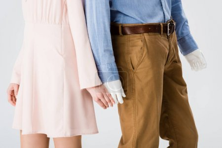 Photo for Cropped view of girl holding hands with mannequin isolated on grey - Royalty Free Image