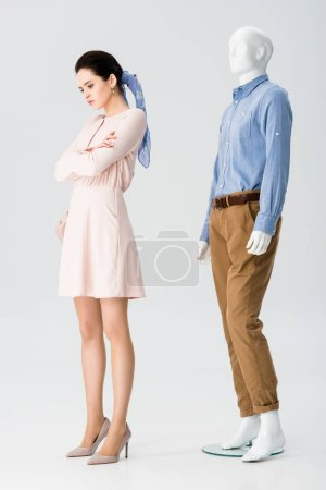 Photo for Beautiful upset girl with crossed arms near mannequin on grey - Royalty Free Image