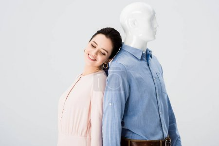 Photo for Beautiful smiling girl posing with mannequin isolated on grey - Royalty Free Image