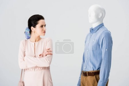 Photo for Beautiful dissatisfied girl with crossed arms looking at mannequin isolated on grey - Royalty Free Image
