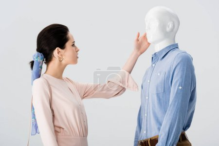 Photo for Beautiful girl stroking mannequin isolated on grey - Royalty Free Image