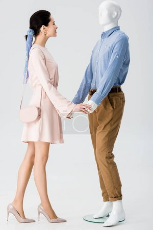 Photo for Beautiful girl holding hands with mannequin isolated on grey - Royalty Free Image