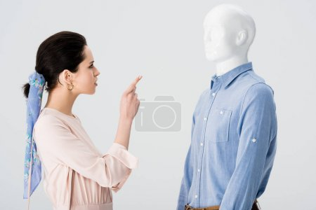 Photo for Dissatisfied girl arguing and pointing with finger at mannequin isolated on grey - Royalty Free Image