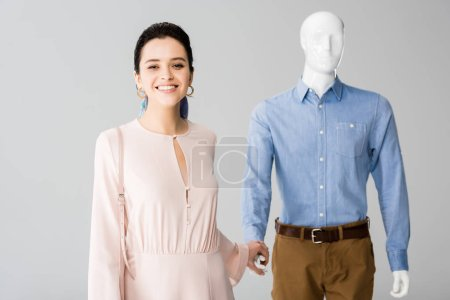 Photo for Beautiful smiling girl holding hands with mannequin isolated on grey - Royalty Free Image