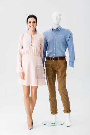 Photo for Beautiful smiling girl holding hands with mannequin on grey - Royalty Free Image