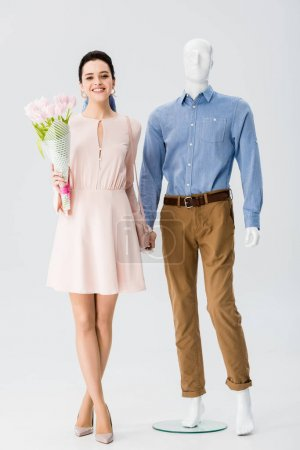Photo for Beautiful girl with flower bouquet holding hands with mannequin on grey - Royalty Free Image