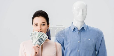 Photo for Panoramic shot of beautiful girl near mannequin holding money isolated on grey - Royalty Free Image