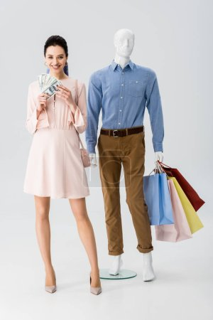 Photo for Beautiful girl holding money while mannequin holding shopping bags on grey - Royalty Free Image