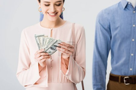 beautiful smiling girl near mannequin counting money isolated on grey
