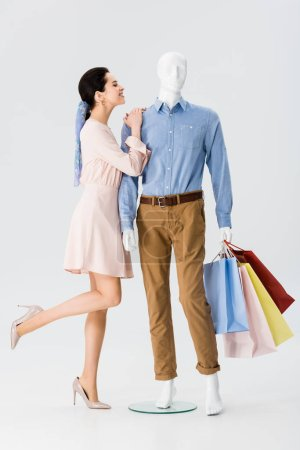 Photo for Beautiful girl leaning on mannequin with shopping bags on grey - Royalty Free Image