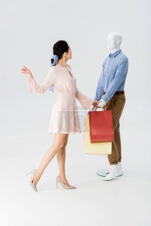 Photo for Beautiful girl gesturing near mannequin with shopping bags on grey - Royalty Free Image