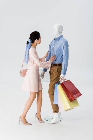 Photo for Beautiful girl pushing mannequin with shopping bags isolated on grey - Royalty Free Image
