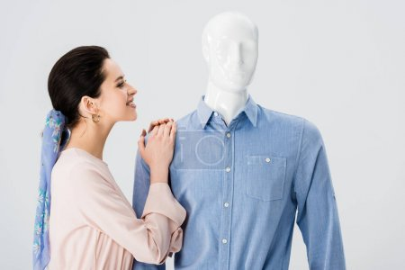 Photo for Beautiful smiling girl leaning on mannequin isolated on grey - Royalty Free Image