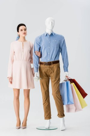 Photo for Beautiful girl holding hand of mannequin with shopping bags on grey - Royalty Free Image