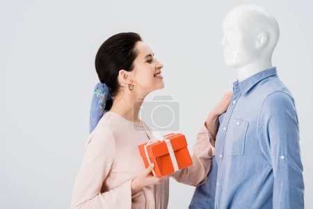 Photo for Beautiful smiling girl with gift box looking at mannequin isolated on grey - Royalty Free Image