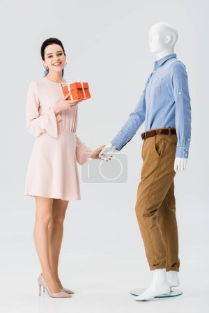 Photo for Beautiful girl with gift box holding hands with mannequin isolated on grey - Royalty Free Image